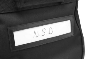 Close up detailed photo of white name card holder with 3 initials saying N.S.B